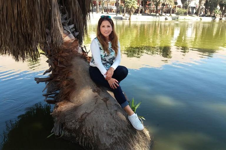 Kobieta siedząca nadrzewie natle jeziora
